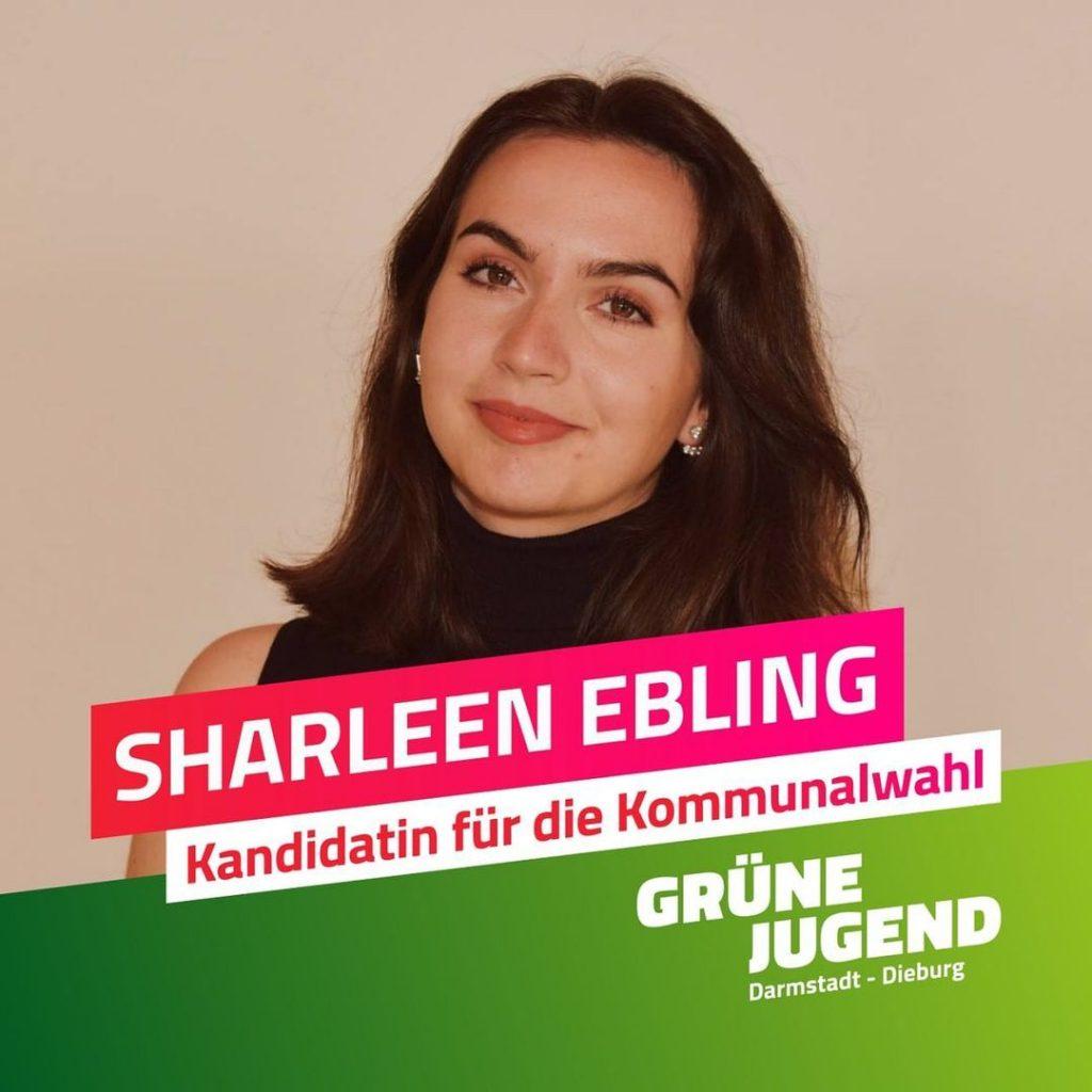 """Ein Bild von Sharleen Ebling, braune Haare und Augen, vor hellem Hintergrund. Im Vordergrund ein Schriftzug mit ihrem Namen und """"Kandidatin für die Kommunalwahl"""" auf pinkem Hintergrund."""