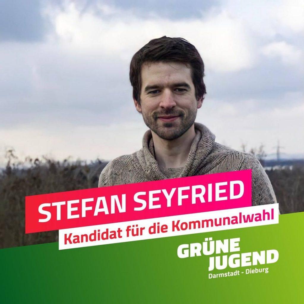 """Ein Bild von Stefan Seyfried. Im Vordergrund ein Schriftzug mit seinem Namen und """"Kandidat für die Kommunalwahl"""" auf pinkem Hintergrund."""